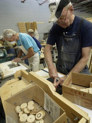 Gary Reeder (right) of the Carmel Golden K Kiwanis Club works with a router to smooth out the wood on the wheel for on a toy car at the Robert Udell Woodworking shop inside Janus Development Services, Noblesville on Friday, November 9, 2007. (James Yee / The Indianapolis Star)