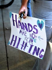 A walker holds a freshly painted sign as the Faith House sponsors a walk to raise awareness for domestic violence Friday evening at Girard Park.