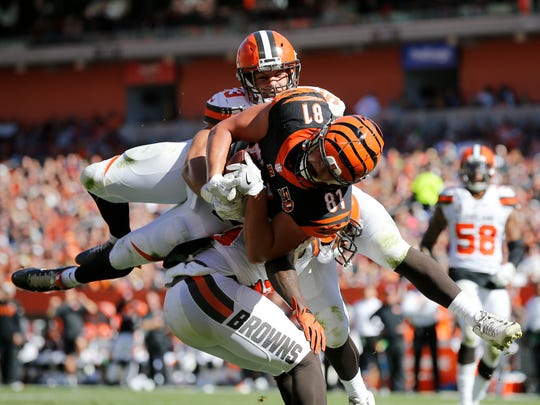 """Cincinnati Bengals tight end Tyler Kroft (81) is up ended as he goes up top for a touchdown reception in the third quarter of the NFL Week 4 game between the Cleveland Browns and the Cincinnati Bengals at FirstEnergy Stadium in downtown Cleveland on Sunday, Oct. 1, 2017. The Bengals tallied their first win of the season, 31-7, in the """"Battle for Ohio"""" game."""