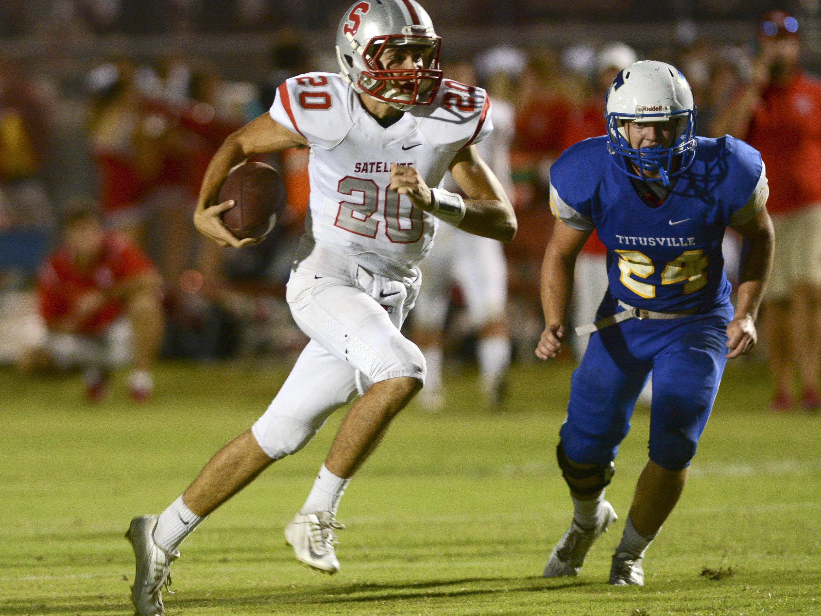 Satellite QB Seth Kennedy (20) is pursued by Titusville's Jacob Farris as he gets into the open field during Friday's game.