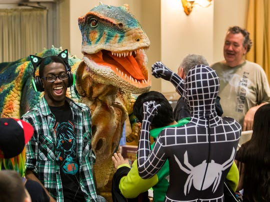A comic book fan dressed as Spiderman takes on a dinosaur at the First State Comic Con at the Mill Creek Fire Hall on Sunday morning.