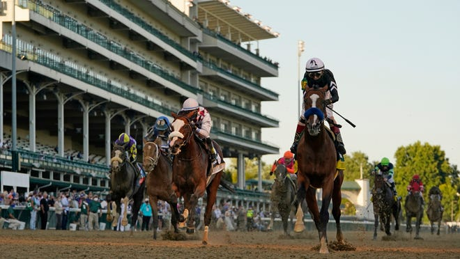 Jockey John Velazquez riding Authentic, right, crosses the finish line to win the 146th running of the Kentucky Derby at Churchill Downs.