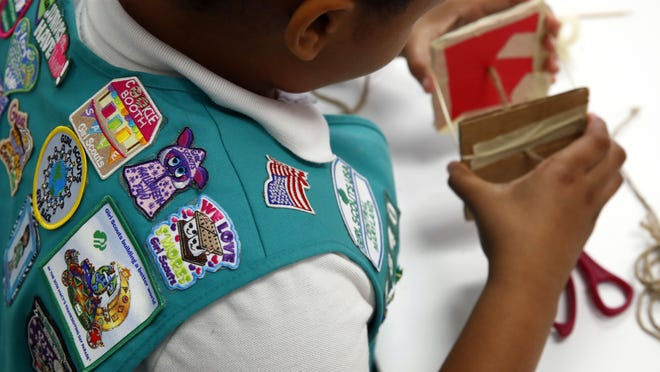 Badges are seen on the vest of a member of the Girl Scouts of Central Maryland as she participates in an activity introducing the world of robotics.