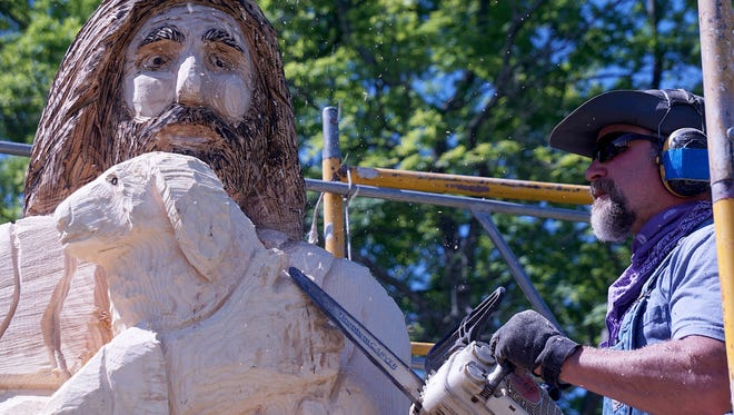 Matt Missey of New London turns a tree into a sculpture depicting Jesus holding a lamb outside the Oakland Lutheran Church on Thursday.