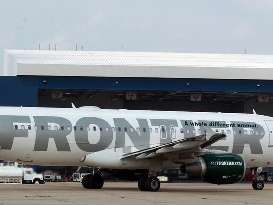 A Frontier Airlines A320 Airbus passes a Delta hangar