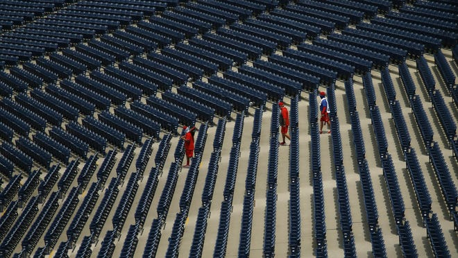 Philadelphia Phillies' personnel walk through empty stands at Citizens Bank Park on Tuesday. A 60-game season is scheduled to start July 23.