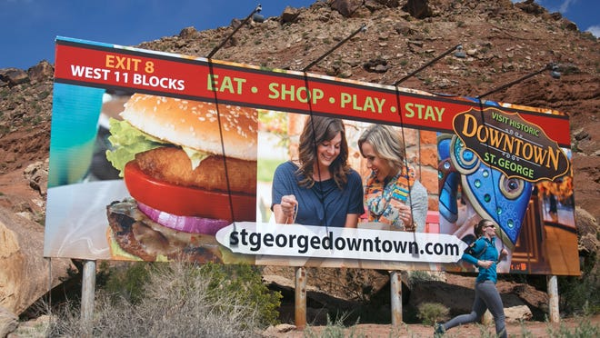 The billboard on Interstate 15 just south of the Virgin River proclaimed St. George as the home of baseball's Bruce Hurst in November of 1986, just after Hurst and the Boston Red Sox lost the 1986 World Series to the New York Mets as can be seen in the then photo taken by Spectrum photographer Nancy Rhodes. The billboard still exists today although it has been changed several times since 1986. The St. George City trail system now includes a section of the Bloomington Hills trail that runs right in front of the billboard as is evidenced by a jogger running past the sign in the now image taken by The Spectrum's Jud Burkett.