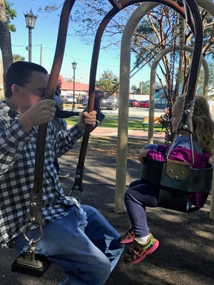 Isabella and her father, Daddy Duty columnist Tim Walters, swing on a dual swing at Taylor Park in Cocoa Village.