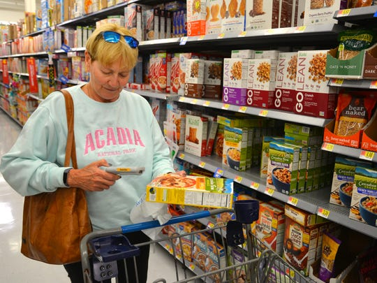 Kathleen Collins scans the barcode on a box of cereal she was buying. Walmart has started a new service called Scan & Go to make shopping easier and checkout quicker.  You pick up a handheld scanner that fits in the cart, scan your items as you shop and then just scan and pay at the self checkout terminal.