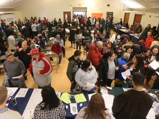 A packed room of families from Puerto Rico attend a welcome reception at the Ibero-American Action League where two dozen agencies came together to provide aid to the families.