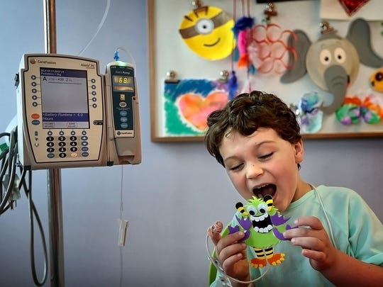 Le Bonheur Children's Hospital patient Graham Carter, 5, puts on his best monster face after finishing a monster during art therapy at the hospital. The hospital is collaborating with the Memphis College of Art for a second year with MCA students, faculty and staff reimagining monsters originally created by the hospital's child patients.
