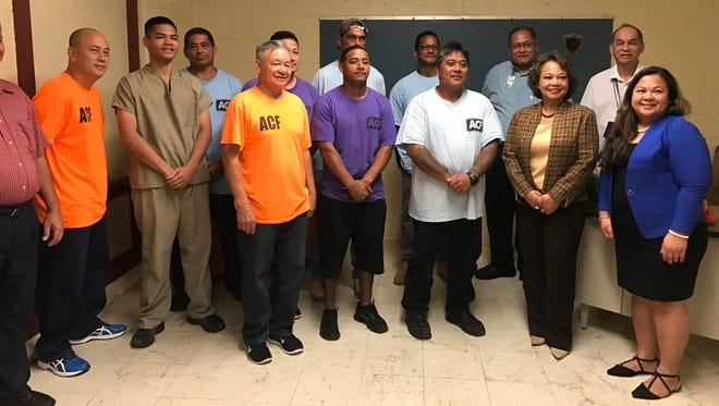 Inmate students and instructors with officials from Guam Department of Labor and Department of Corrections at a press conference Nov. 29.