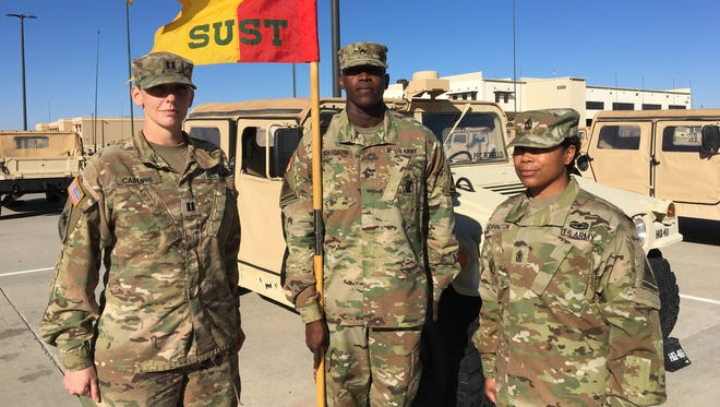 Capt. Kelcee Capurs, left, and 1st Sgt. Stephanie Washington, right, are the command team for Headquarters and Headquarters Company, Special Troops Battalion. Staff Sgt. Jeremy Thompson is holding the company guidon.