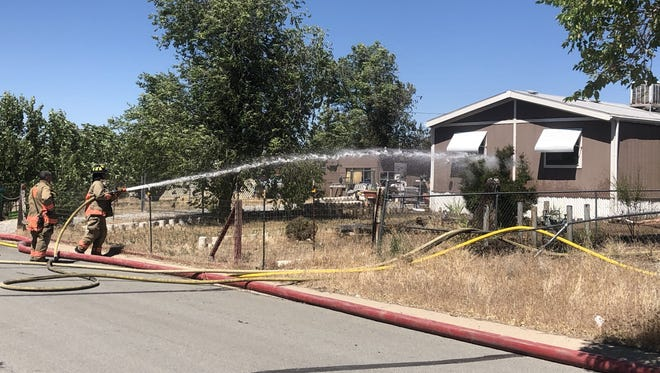 Fire crews work to put out flames that started as a brush fire in Sun Valley on Thursday, July 5, 2018. Two homes sustained minor damage and one trailer was a total loss.