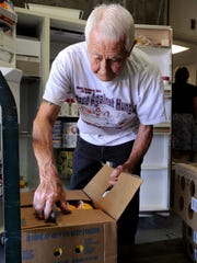 Mago Villegas, 85, puts cartons of milk into a refrigerator at  the Visalia Emergency Aid Council. He's been volunteering there for nine years and was at FoodLink before that for 8 years. Cash donations and fresh produce are needed at the nonprofit as more families than ever are asking for aid.