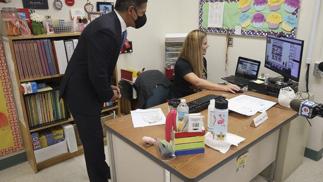 Miami-Dade County Public Schools superintendent Alberto Carvalho leans over to greet students remotely during a visit to Ms. Vanessa Acosta's first grade class during a brief visit to Bob Graham Education Center in Miami Lakes, Fla., on Aug. 31.