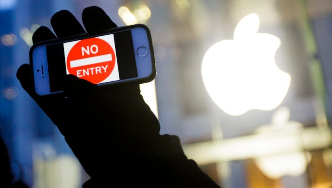 In a file photo from Feb. 23, 2016, a man holds up an iPhone at a rally supporting Apple's privacy policy in New York.