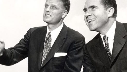 Evangelist Billy Graham, left, and then-Vice President Richard Nixon relax during a break in a conference in Montreat in 1956.