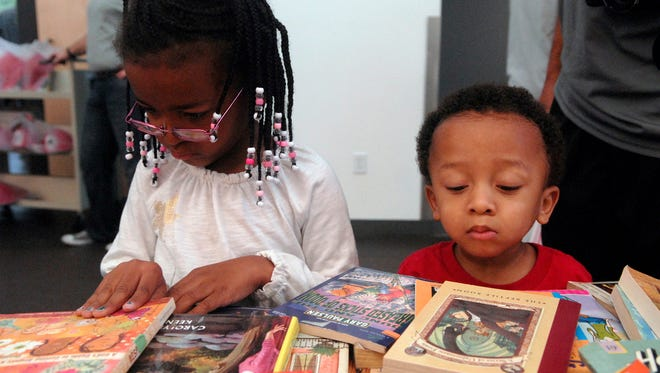 Keilani Gibson, 5, left, and her brother Kasen, 2, right, look over the free books during Share A Story, Make A Difference Day at the Southwest branch of the Louisville Free Public Library. October 24, 2015