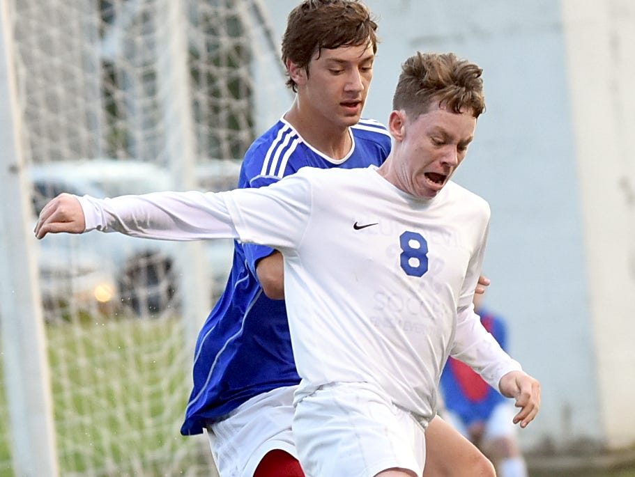 White House High junior Austin Blansett maintains possession amidst pressure from Page sophomore Will Pierce during first-half action.