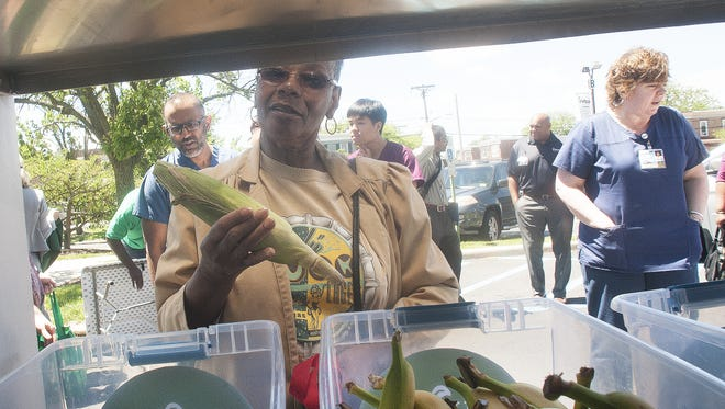 Juanita Hicks of Camden shops for produce at the Virtua Mobile Farmers Market at Virtua Camden on Monday. The health system's market on wheels offers fresh produce and nutritional advice in neighborhoods with higher rates of chronic disease and food insecurity.