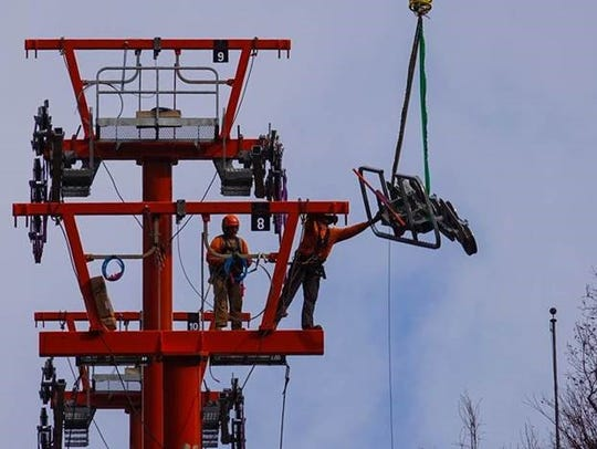 Workers grab parts from a helicopter to rebuild the