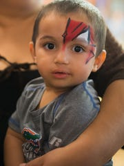 Juan Pedro Nino-Brown gets his face painted in the arms of Minerva Ollervides, Sunday, July 29, at a celebration for him and his brother at American Legion Hall.