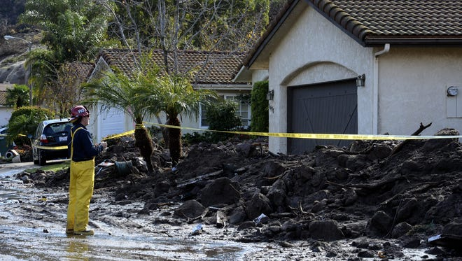 A fireman surveys homes affected by a mud and rock slide  in the Ventura County town of Camarillo, California, USA, 12 December 2014 following a strong storm. The area of Camarillo, 50 miles north of Los Angeles, affected by the massive rock slide was the scene of the Camarillo Springs Fire this summer.