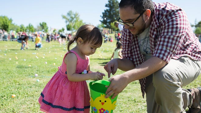 Josh Tenorio,right, helps his daughter Kaia Tenorio, 2, as she collects eggs at the egg hunt during Springfest 2017 at Young Park, Saturday, April 15, 2017. There were 16,000 eggs put out on the field at Young Park for kids to collect during the egg hunts.