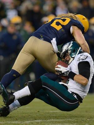 Packers linebacker Clay Matthews (52) sacks Eagles quarterback Mark Sanchez in the second quarter Sunday at Lambeau Field.