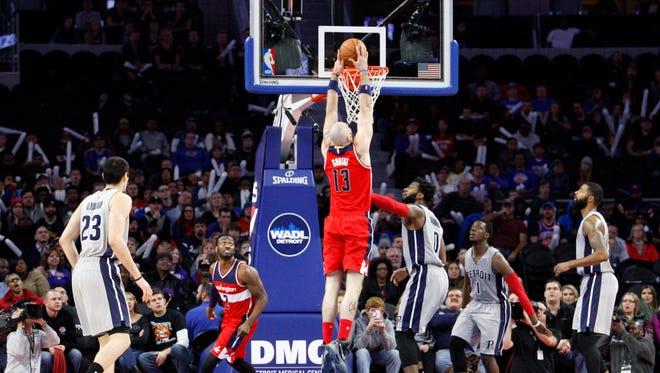 Nov 21, 2015; Auburn Hills, MI, USA; Washington Wizards center Marcin Gortat (13) makes a dunk on Detroit Pistons center Andre Drummond (0) during the fourth quarter at The Palace of Auburn Hills. Wizards win 97-95.