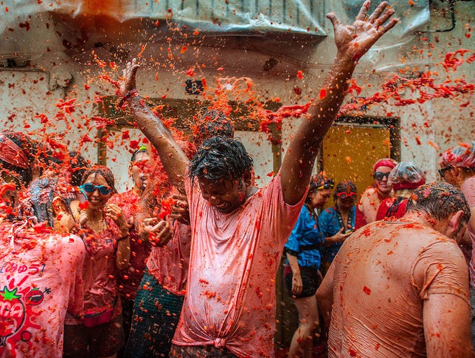 People are covered with tomato pulp at the annual Tomatina Festival on Aug. 28 in Bunol, Spain. Twenty thousand people threw 130 tons of ripe tomatoes in the world's biggest tomato fight.