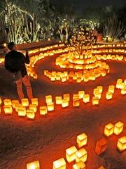 Visitors walk through a spiral of luminarias in November