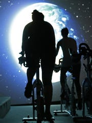 Students pedal toward an image of the Earth as seen from outer space in a spinning class at Brooklyn's IMAXShift in New York. Participants pedal on stationary bicycles as images flash by on a giant IMAX screen in a theater-like setting.