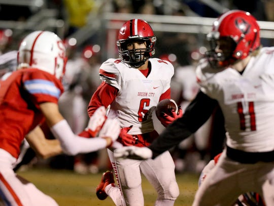 Oregon City's Trevon Bradford (6) looks for a hole to run through in the Oregon City vs. South Salem class 6A playoffs football game at South Salem High School on Friday, Nov. 13, 2015.