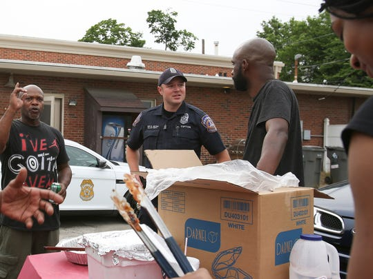 """Officers of the Indianapolis Metropolitan Police Department, Javed Richards and Calvin Tipton speak with Andre Green and Charles Lovelady on 10th Street in Downtown Indianapolis on June 3, 2016. Green and Lovelady make BBQ to give out to the community for free. """" It's so nice to see people doing good things for the community, we don't get to see a lot of the good,"""" said Tipton."""