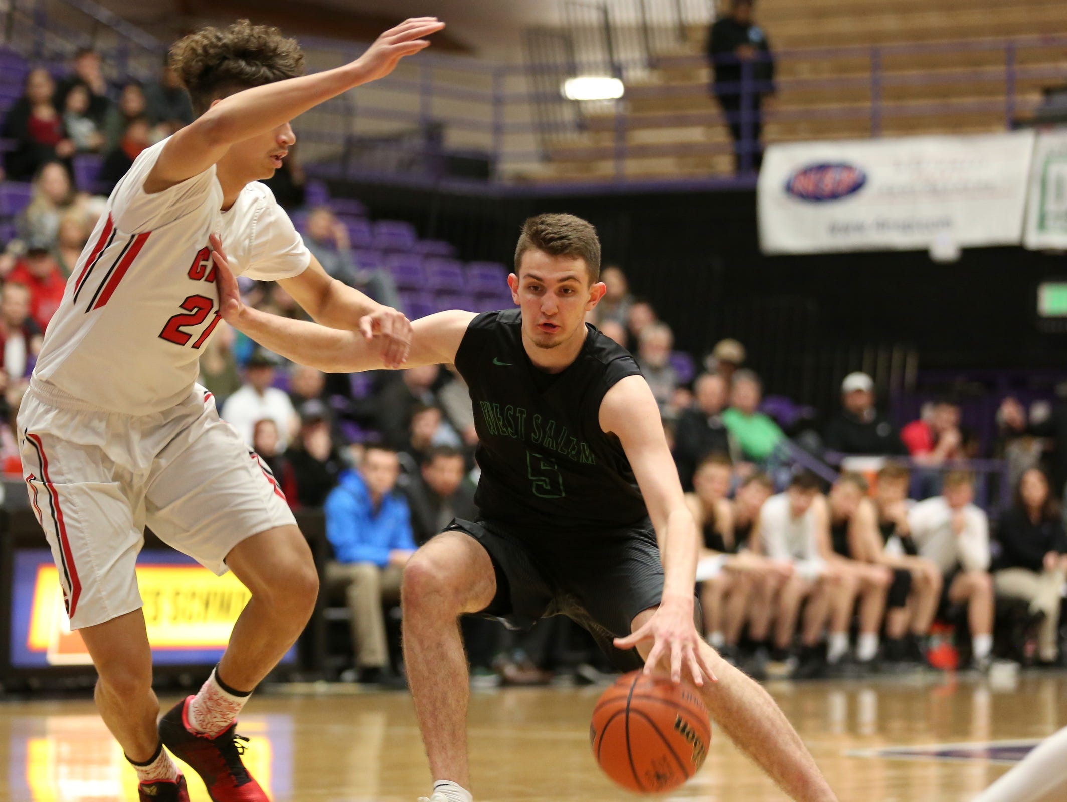 West Salem's Kyle Greeley (5) moves past Clackamas' Cole Turner (21) during the first half of the West Salem vs. Clackamas boy's basketball game in the quarterfinals of the OSAA Class 6A State Championships at the University of Portland on Wednesday, March 8, 2017. Clackamas won the game 68-52. West Salem will play a consolation game on Thursday.