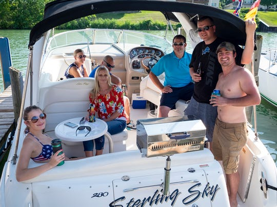 Groups of people hang out on boats on Boat Night Friday, July 13, 2018, during Boat Week in Port Huron.