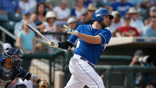 Kansas City Royals third baseman Mike Moustakas (8) hits a single in the fourth inning against the San Diego Padres during a spring training game at Surprise Stadium on March 11, 2015, in Surprise.