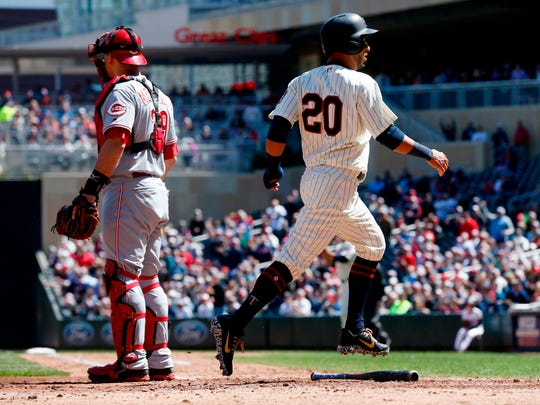 Minnesota Twins' Eddie Rosario, right, scores on a triple by Eduardo Escobar off Cincinnati Reds' pitcher Sal Romano in the fourth inning of a baseball game Saturday, April 28, 2018, in Minneapolis.