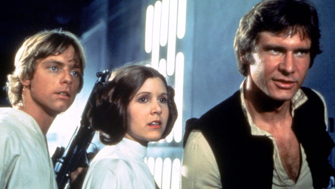 """A scene from the 1977 """"Star Wars"""" movie features Mark Hamill as Luke Skywalker, from left, Carrie Fisher as Princess Leia Organa and Harrison Ford as Han Solo."""