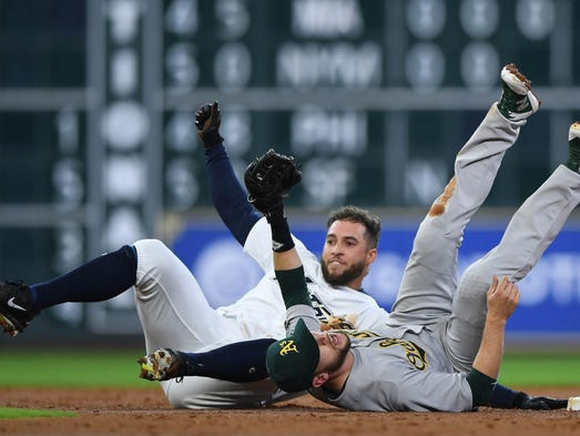 The Astros' George Springer, left, collides with Athletics