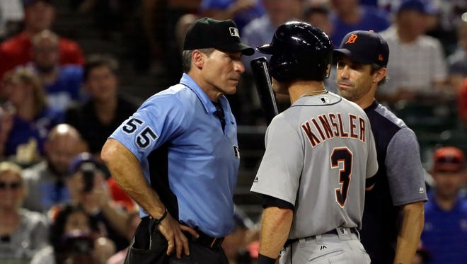 Home plate umpire Angel Hernandez listens to Tigers second baseman Ian Kinsler and manager Braud Ausmus.