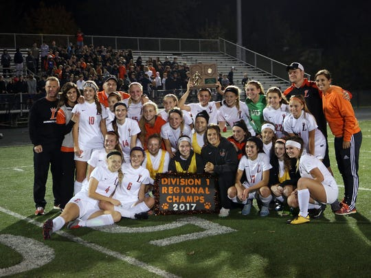 The Loveland Tigers pose with the Regional Championship Trophy after the Regional final match between Loveland and Springboro at Lebanon Junior High School in Lebanon, Ohio. Loveland defeated Springboro 1-0 with 1:19 left in 1OT.