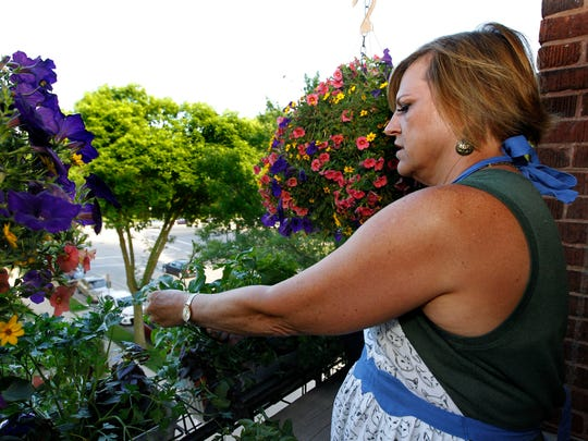 Vicki Brown picks arugula from her balcony vegetable garden.