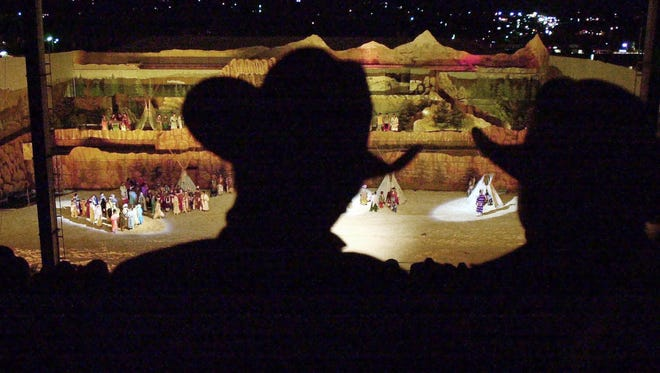 Two men in cowboy hats are silhouetted against an elaborate set for the night show during the Pendleton Round-Up in 2003.