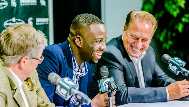 Former MSU basketball player, Draymond Green, center, smiles as MSU Men's Basketball Head coach Ton Izzo, right and MSU President LouAnna K. Simon ,left, look on smiles during a press conference annoucing his a $3.1 million donation to MSU athletics and the scholarship fund Thursday at the Breslin Center in East Lansing.