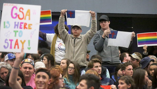 Before a Franklin County School Board meeting in February, Colton Elliot, left, and Luke Housley, right, hold Christian flags as they are surrounded by supporters of the Gay-Straight Alliance club that formed at the county's high school in January.