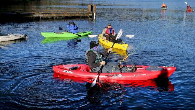 Active duty Army veteran master sergeant Milton Pate Jr., foreground, stationed at JBLM, is bundled up as he heads out in a kayak to fish at Kitsap Lake on Saturday morning. He was participating in the Heroes on the Water event.