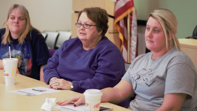 Courtney Marks, Judy Burkhart and Anna Walker listen to fellow members during a twice-weekly support group for parents with children diagnosed on the autism spectrum.